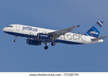 "NEW YORK - JANUARY 30: Airbus A320 of JetBlue Airlines, wearing new livery called ""barcode"", on final approach to John F Kennedy International Airport on January 30, 2011 in New York, USA - stock photo"