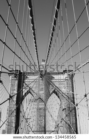 NEW YORK - JANUARY 6: American flag on top of famous Brooklyn Bridge on January 6, 2013. The Brooklyn Bridge opened in 1883. At the time, it was the longest suspension bridge. - stock photo