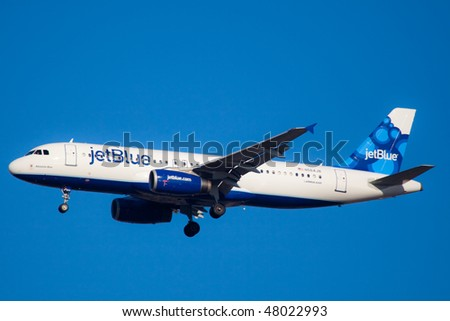 "NEW YORK - JANUARY 9: An Airbus A320 jet Blue with new tail design ""blueberries""  lands at JFK Airport on Runaway 31R on January 9, 2010 in New York. - stock photo"