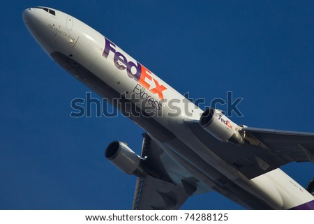 NEW YORK - JANUARY 20: McDonnell Douglas MD-11 Fedex Climbs after take of from JFK in New York, USA on January 20, 2011. Fedex Express is the biggest cargo/mail carrier company in the world - stock photo