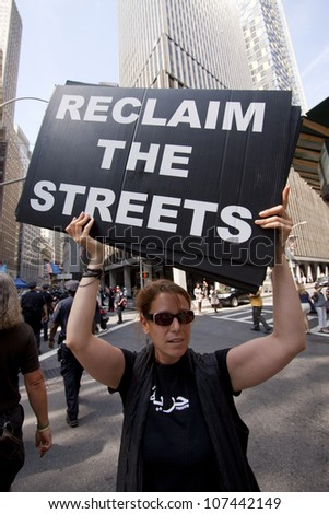 NEW YORK-JULY 11: A protester holds a sign that says 'Reclaim The Streets' at the Occupy Guitarmy march in Lower Manhattan during the #99MileMarch from Philly to NYC on July 11, 2012 in New York, NY. - stock photo