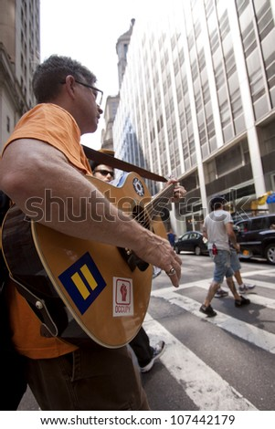 NEW YORK-JULY 11: An Occupy Guitarmy protester plays his guitar while walking up Broad St in Lower Manhattan during the #99MileMarch from Philly to NYC on July 11, 2012 in New York, NY. - stock photo