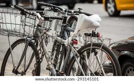 NEW YORK - JULY 19, 2014: chained bicycles parked on Manhattan, New York City street, in NY. Delivery persons and messengers use bicycles for transportation throughout the 5 boroughs of New York. - stock photo