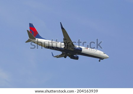 NEW YORK - JULY 8: Delta Airlines Boeing 737 in New York sky before landing at JFK Airport on July 8, 2014. Delta Air Lines and its subsidiaries operate over 5000 flights every day - stock photo