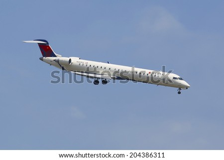 NEW YORK - JULY 8  Delta Connection Bombardier CRJ-900 in New York sky before landing at JFK Airport on July 8, 2014  Delta Air Lines and its subsidiaries operate over 5000 flights every day
