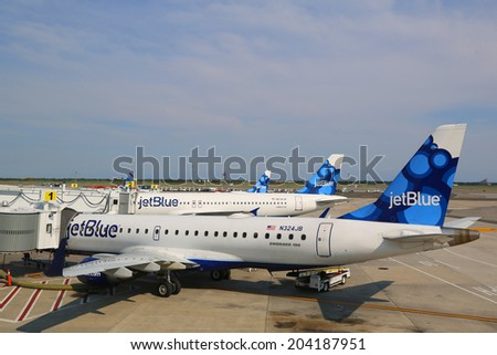 NEW YORK- JULY 10: JetBlue Airbus A320 and  Embraer 190 aircraft at the gates at the Terminal 5 at John F Kennedy International Airport in New York on July 10, 2014 - stock photo