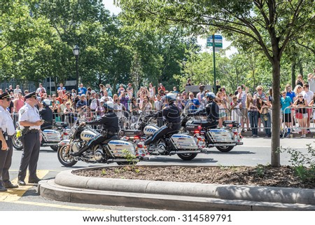 NEW YORK - JULY 10: Police officers drive motorcycles during the  parade on July 10, 2015 in NYC. The parade has been organized to celebrate the U.S. women's soccer team's World Cup final win. - stock photo