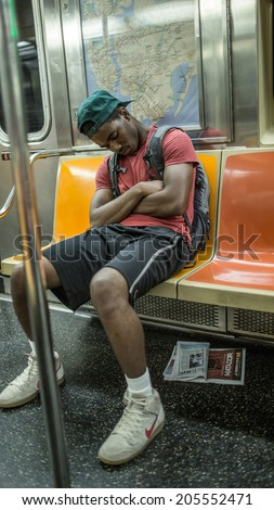 NEW YORK - JULY 14, 2014: teen sleeps on MTA subway train in New York. The NYC Subway is a rapid transit/transportation system in the City of NY. - stock photo