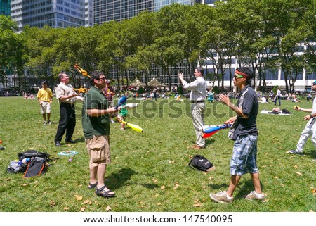 NEW YORK - JULY 26:  The Bryant Park Jugglers teach others and enjoy Juggling with one another in Bryant Park July 26, 2013 in New York City.