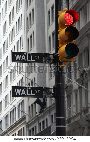 NEW YORK - JUNE 20: A symbolic photo of Wall street signs with a red traffic light on June 20, 2011 in New York. The red light is a symbol of the crisis on the way. - stock photo