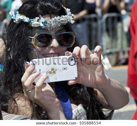 NEW YORK - JUNE 23: Actress Annabella Sciorra as Queen Mermaid takes pictures with iPhone at 30th annual Mermaid parade on Coney Island in Brooklyn on June 23, 2012 in New York City.