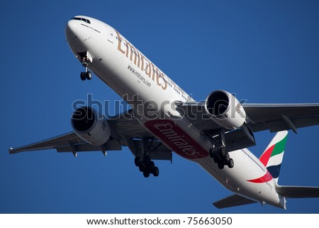 NEW YORK - JUNE 10: Boeing 777 Emirats on final approach to JFK airport located in New York, NY on June 10, 2010. Emirates is rated as a top10 best airline in the world flying on youngest fleet - stock photo