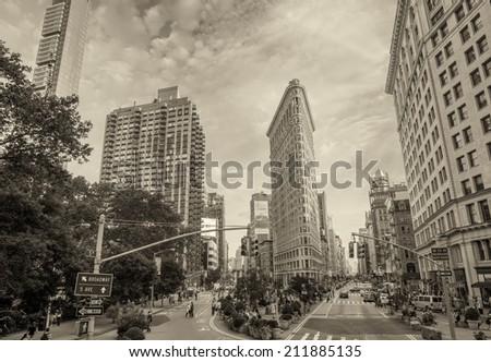 NEW YORK - JUNE 15, 2013: Flat Iron building facade with tourists on the streets. Completed in 1902, it is considered to be one of the first skyscrapers ever built - stock photo