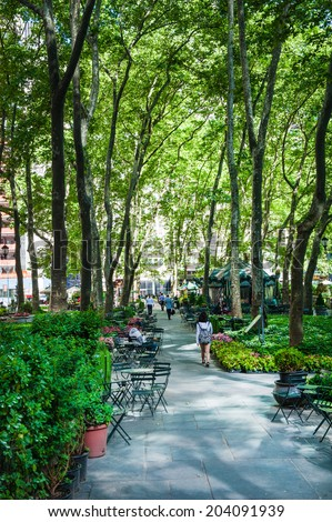 NEW YORK - June 08: People are walking in Bryant Park on June 08 2014 in Manhattan. Bryant Park is a popular 9.6 acre park located adjacent to The NY Public Library. - stock photo
