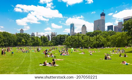 NEW YORK - JUNE 14: People enjoying relaxing outdoors in Central Park on June 14, 2014 in New York. The park is the most visited urban park in the United States with 35 million visitors annually. - stock photo
