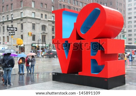 NEW YORK - JUNE 7: People walk past Love sculpture in rain on June 7, 2013 in New York. The famous monument by Robert Indiana is located on 6th Avenue. - stock photo