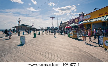 NEW YORK - JUNE 27: Riegelmann Boardwalk with Parachute Jump in the background on June 27, 2012 in Coney Island, NY. The Parachute Jump is 262 feet (80 m) tall and weighing 170 tons (150 tonnes). - stock photo