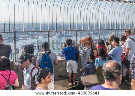 New York, June 19, 2016: Tourists are enjoying the spectacular views from the main observation deck of Empire State Building - stock photo