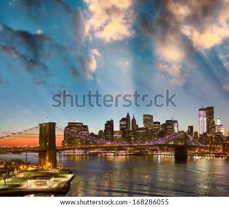 New York. Lights of city skyline and Brooklyn Bridge as seen from Manhattan Bridge. - stock photo
