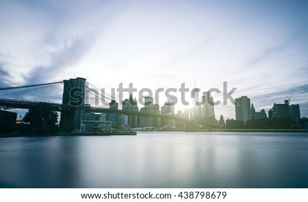 New york long exposure photo at dusk time. Manhattan skyline and Brooklyn bridge with cold tones - stock photo