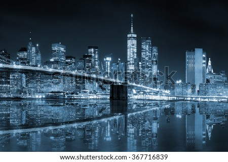 New York - Manhattan Skyline with skyscrapers and famous Brooklin Bridge by night with reflection, black and white blue toned - stock photo