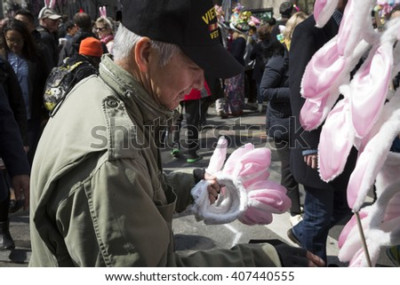 NEW YORK - MAR 27 2016: A street vendor holds several pairs of pink and white bunny ears to sell on Easter Sunday during the traditional Easter Bonnet Parade in Manhattan on March 27, 2016. - stock photo