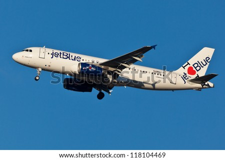 NEW YORK - MARCH 20: A320 jetBlue approaching JFK in New York, USA on March 20, 2012. Plane is wearing special livery called I love blue york jetBlue as of 2011 is fastest growing airline in world - stock photo