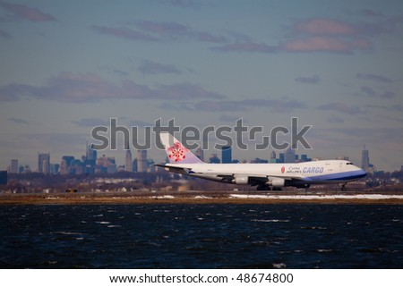 NEW YORK -MARCH 1:Boeing 747 Air China Cargo departing from JFK Airport on Runaway 4L with Manhattan skyline in background on March 1, 2010 in New York. Picture taken from Bayswater Park