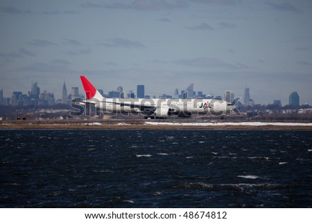 NEW YORK -MARCH 1:Boeing 777 Air JAL Japan  JFK Airport on Runaway 4L with Manhattan skyline in background on March 1, 2010 in New York. Picture taken from Bayswater Park