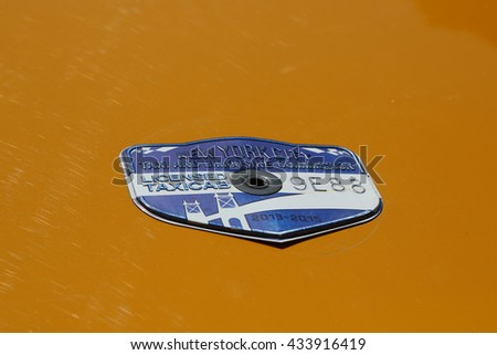 NEW YORK - MARCH 29, 2015: New York City taxi medallion in New York. Canary yellow in color, medallion taxis are able to pick up passengers anywhere in the five boroughs. - stock photo