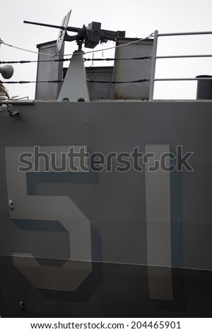 NEW YORK - MAY 22: A machine gun on the deck above the ships number 51 painted on the hull of the amphibious dock landing ship USS Oak Hill (LSD 51) at Pier 92 during Fleet Week NY on May 22, 2014.