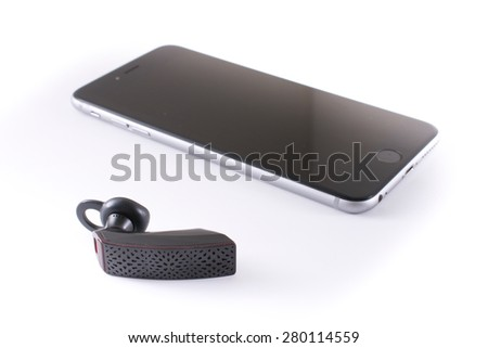 NEW YORK - May 21, 2015: A modern Jawbone Era Bluetooth headset with an iPhone 6 plus isolated on white - illustrative editorial