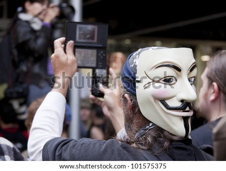 NEW YORK - MAY 1: A protester wearing a Guy Fawkes mask records the march to Union Square from Bryant Park on two mobile devices at Occupy Wall St 'May Day' protests on May 1, 2012 in New York, NY. - stock photo