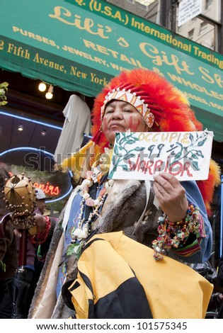 NEW YORK - MAY 1: A protester wearing a red headdress holds a sign that reads '99% Warrior ' during the march to Union Square at Occupy Wall St 'May Day' protests on May 1, 2012 in New York, NY. - stock photo