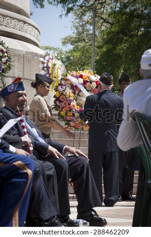 NEW YORK - MAY 25 2015: A US veteran helps lay a wreath of flowers at the annual Memorial Day Observance service held at the Soldiers and Sailors Monument in Manhattan during Fleet Week NY 2015. - stock photo