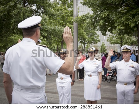 NEW YORK - MAY 22 2015: Admiral Phil Davidson, Commander, US Fleet Forces Command, swears in personnel during the re-enlistment and promotion ceremony at the National September 11 Memorial site. - stock photo