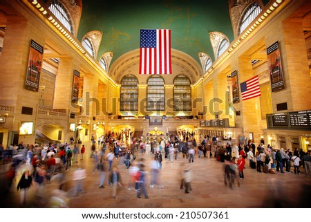 NEW YORK - MAY 20, 2006: Couple pauses to embrace as other commuters rush about Grand Central Terminal in New York City on May 20, 2006. - stock photo