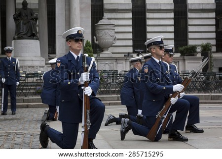 NEW YORK - MAY 21 2015: Members of the US Coast Guard Ceremonial Honor Guard Silent Drill Team kneel down during a drill next to the New York Public Library in Bryant Park during Fleet Week NY 2015. - stock photo