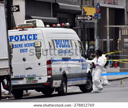 NEW YORK - MAY 13: NYPD Crime scene investigators probe the scene of a shooting in Midtown New York on May 13, 2015. The shooting occurred between police and a criminal fugitive. - stock photo