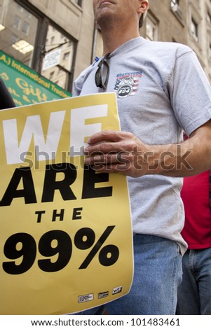 NEW YORK - MAY 1: Protesters march to Union Square from Bryant Park during Occupy Wall St 'May Day' protests on May 1, 2012 in New York, NY. Slogans on signs include 'We Are The 99 percent'. - stock photo