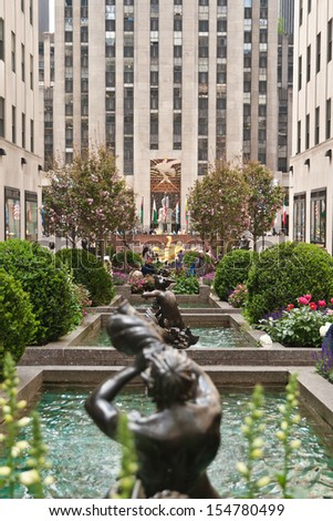 NEW YORK - MAY 7: Sculptures and decoration on gardens in Rockefeller Center in the front and Prometheus monument and flags behind. Taken on May 7, 2013, in New York City, USA. - stock photo
