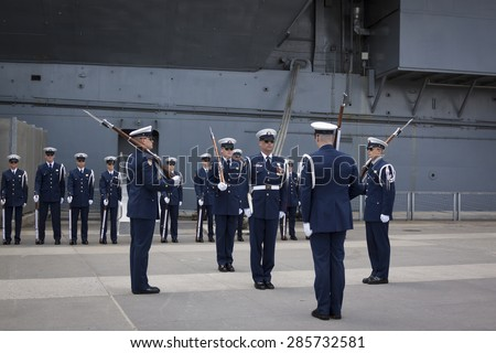 NEW YORK - MAY 22 2015: The US Coast Guard Ceremonial Honor Guard Silent Drill Team perform on Pier 92 next to the Intrepid Sea, Air, and Space Museum during Fleet Week NY 2015. - stock photo