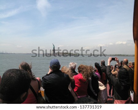 NEW YORK - MAY 7: Tourists look towards the Statue of Liberty while on a Staten Island Ferry on May 7, 2013 in New York.