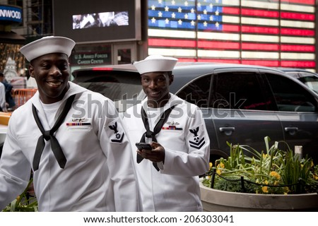 NEW YORK - MAY 23: Two US Navy sailors on liberty pass the lighted US Flag on the Armed Forces Recruiting Center in Times Square during Fleet Week NY.                                                   - stock photo