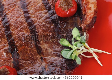 new york meat style beef steak fillet on red plate with hot chili pepper and green salad isolated over white background with stainless steel cutlery - stock photo