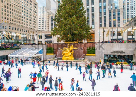 NEW YORK, NEW YORK - DECEMBER 25: Many people, ice skaters and tourists, are all around the famous Rockefeller Center Christmas tree on December 25, 2014, Christmas, in Midtown of Manhattan.   - stock photo