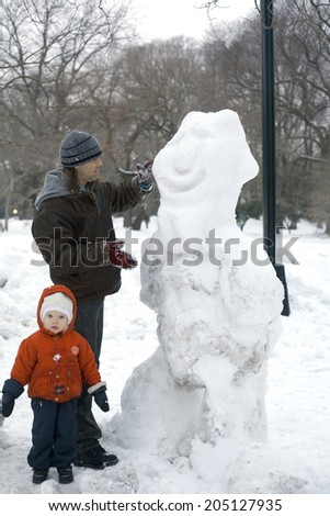 NEW YORK, NEW YORK - JANUARY 25: A father and child build a snowman in Central Park.   Taken January 25, 2011 in NYC.  - stock photo