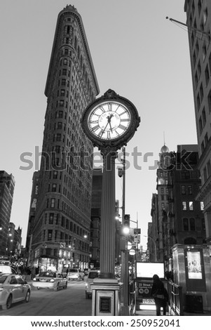NEW YORK, NEW YORK - JANUARY 31, 2015: Flatiron Buliding and Fifth Avenue Clock. Completed in 1902, it is considered to be one of the first skyscrapers ever built.