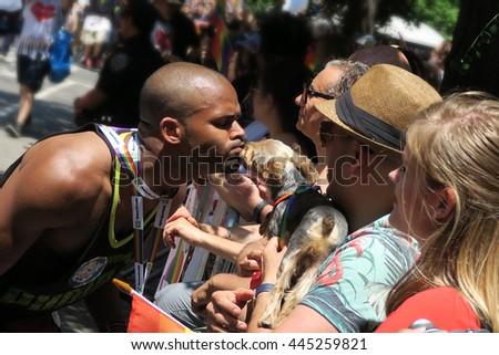 NEW YORK, NEW YORK - JULY 26, 2016: Man kissing a dog at the Gay Pride Parade on 5th avenue. Editorial use only.  - stock photo