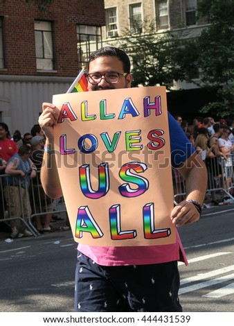 "NEW YORK, NEW YORK - JULY 26, 2016: Man marching in Gay Pride Parade on 5th avenue. He is holding a sign that says, ""ALLAH LOVES US ALL."" Editorial use only.  - stock photo"